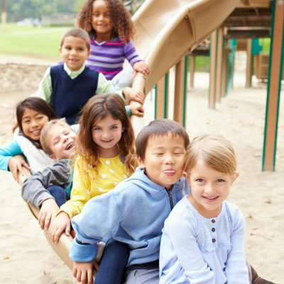 Group Of Young Children Sitting On Slide In Playground