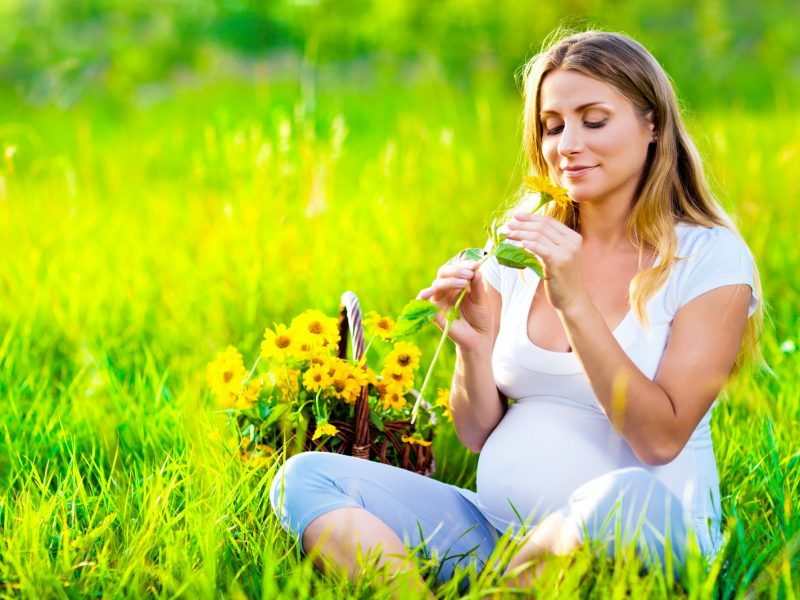 Pregnant woman sitting on green field